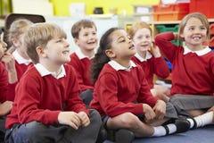 Alumnos que se sientan en Mat Listening To Teacher imagenes de archivo