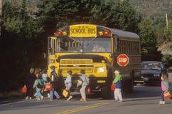 Alumnos que suben a un schoolbus Fotografía de archivo