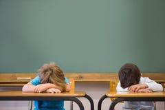 Alumnos soñolientos que toman una siesta en los escritorios en sala de clase Imagen de archivo libre de regalías