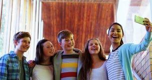 Alumnos sonrientes que toman el selfie con el teléfono móvil en pasillo almacen de video