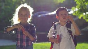 Alumnos un muchacho y una muchacha durante soplo de la hendidura muchas burbujas de jabón en contraluz en el aire abierto metrajes