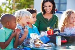 Alumnos y profesor elementales Eating Lunch imagen de archivo