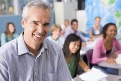 Alumnos y su profesor en clase imagen de archivo