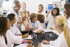 Alumnos y su profesor en clase de la ciencia Imágenes de archivo libres de regalías