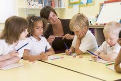 Alumnos y su profesor en clase primaria foto de archivo libre de regalías