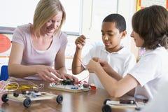 Alumnos y su profesor que aprenden ciencia imagen de archivo