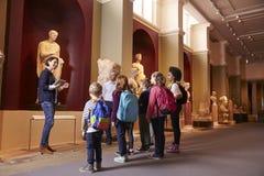 Alumnos y viaje de On School Field del profesor al museo con la guía fotografía de archivo