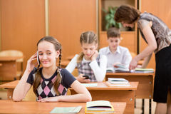 Aluno da escola primária que usa o telefone celular na lição Imagem de Stock