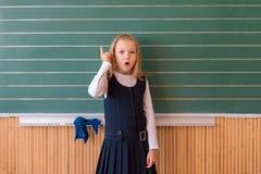 Aluno de primeiro grau uma escrita da menina no quadro-negro verde na lição da escola Foto de Stock Royalty Free