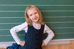 Aluno de primeiro grau uma escrita da menina no quadro-negro verde na lição da escola Fotografia de Stock Royalty Free