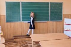 Aluno de primeiro grau uma escrita da menina no quadro-negro verde na lição da escola Imagens de Stock Royalty Free