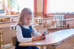 Aluno de primeiro grau uma escrita da menina no quadro-negro verde na lição da escola fotos de stock