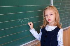 Aluno de primeiro grau uma escrita da menina no quadro-negro verde na lição da escola Imagens de Stock