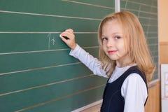 Aluno de primeiro grau uma escrita da menina no quadro-negro verde na lição da escola foto de stock
