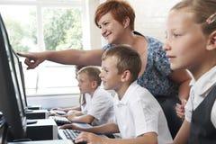 Aluno elementar masculino na classe do computador com professor Fotografia de Stock