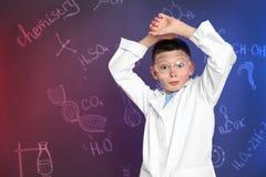 Aluno emocional contra o quadro-negro com fórmulas escritas da química foto de stock