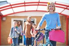 Aluno fêmea que empurra a bicicleta no fim do dia escolar Imagens de Stock Royalty Free