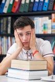 Aluno masculino forçado que trabalha na biblioteca Imagens de Stock