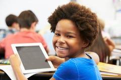 Aluno na classe que usa a tabuleta de Digitas Imagens de Stock