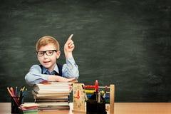 Aluno na sala de aula sobre o fundo do quadro-negro, apontando o menino fotografia de stock