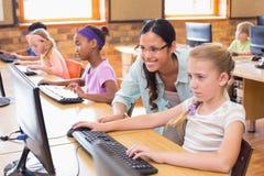 Alunos bonitos na classe do computador com professor imagem de stock royalty free