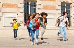 Alunos bonitos que correm do prédio da escola Imagem de Stock