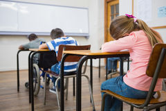 Alunos bonitos que escrevem em mesas na sala de aula Imagem de Stock Royalty Free