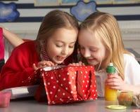 Alunos da escola preliminar que apreciam o almoço embalado em Cla Fotografia de Stock Royalty Free