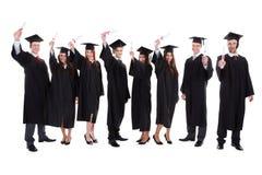 Alunos diplomados que levantam as mãos Fotos de Stock