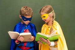 Alunos em trajes do super-herói com livros Imagem de Stock Royalty Free