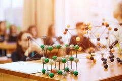 Alunos em uma classe da ciência com um modelo molecular Imagem de fundo com foco macio Conceito da instrução imagens de stock royalty free