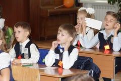 Alunos em uma mesa da escola em uma lição na escola - Rússia Moscou a primeira High School a primeira classe b - 1º de setembro d Foto de Stock Royalty Free