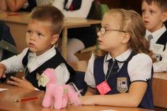 Alunos em uma mesa da escola em uma lição na escola - Rússia Moscou a primeira High School a primeira classe b - 1º de setembro d Fotografia de Stock Royalty Free