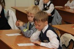Alunos em uma mesa da escola em uma lição na escola - Rússia Moscou a primeira High School a primeira classe b - 1º de setembro d Imagens de Stock Royalty Free