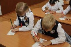 Alunos em uma mesa da escola em uma lição na escola - Rússia Moscou a primeira High School a primeira classe b - 1º de setembro d Fotos de Stock Royalty Free