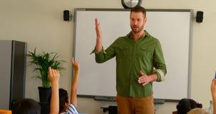alunos Multi-?tnicos que levantam as m?os ao sentar-se na mesa em uma sala de aula na escola 4k vídeos de arquivo