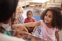 Alunos na escola de Montessori que olha o livro com professor fotografia de stock royalty free