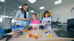 Alunos novos em tecnologias aéreas do estudo de laboratório da pesquisa da escola - zangões, helicópteros, aviões vídeos de arquivo