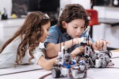 Alunos positivos que apreciam o projeto da tecnologia na escola Fotografia de Stock Royalty Free