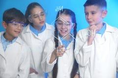 Alunos que estudam a fórmula da química na placa de vidro fotografia de stock royalty free