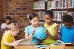 Alunos que estudam o globo na biblioteca imagem de stock royalty free