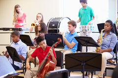 Alunos que jogam instrumentos musicais na orquestra da escola