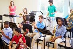 Alunos que jogam instrumentos musicais na orquestra da escola Fotografia de Stock