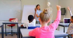 Alunos que levantam a mão ao sentar-se na mesa na escola primária 4k video estoque