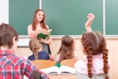 Alunos que levantam suas mãos durante classes Fotografia de Stock