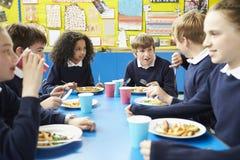 Alunos que sentam-se na tabela que come o almoço cozinhado fotografia de stock royalty free