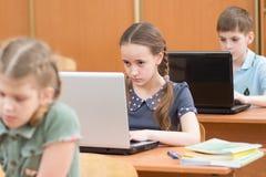 Alunos que usam o portátil na lição na sala de aula imagens de stock royalty free