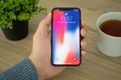 Man hand holding iPhone X with IOS 11 on screen Stock Photography
