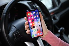 Woman hand holding iPhone X with IOS 11 in car Royalty Free Stock Images