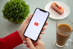 Woman holding iPhone X with app YouTube on the screen royalty free stock photo